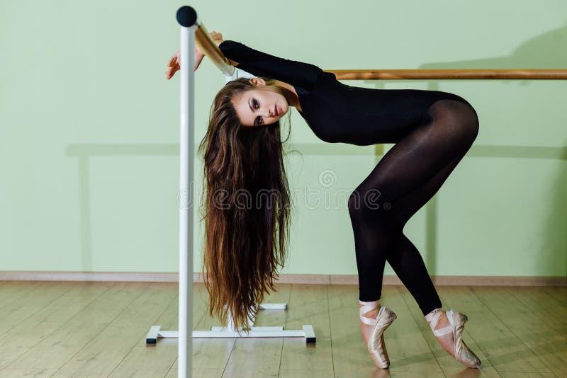 Dançarino bonito novo que levanta na barra do bailado da sagacidade do estúdio na ponta do pé Morena 'sexy' moderna fotos de stock royalty free