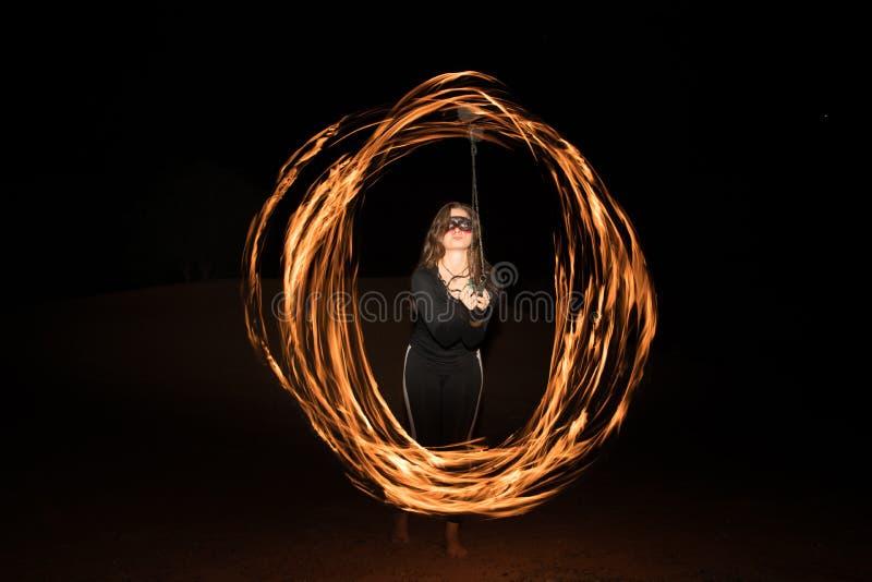 Dançarino com os pois flamejantes do fogo após a obscuridade foto de stock