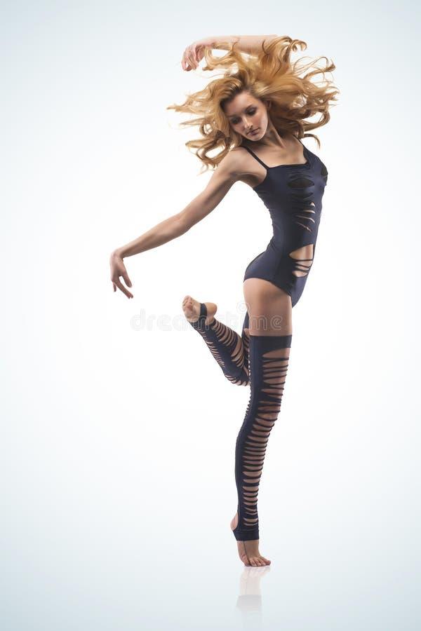 Dançarino consideravelmente moderno da mulher no fundo azul imagem de stock