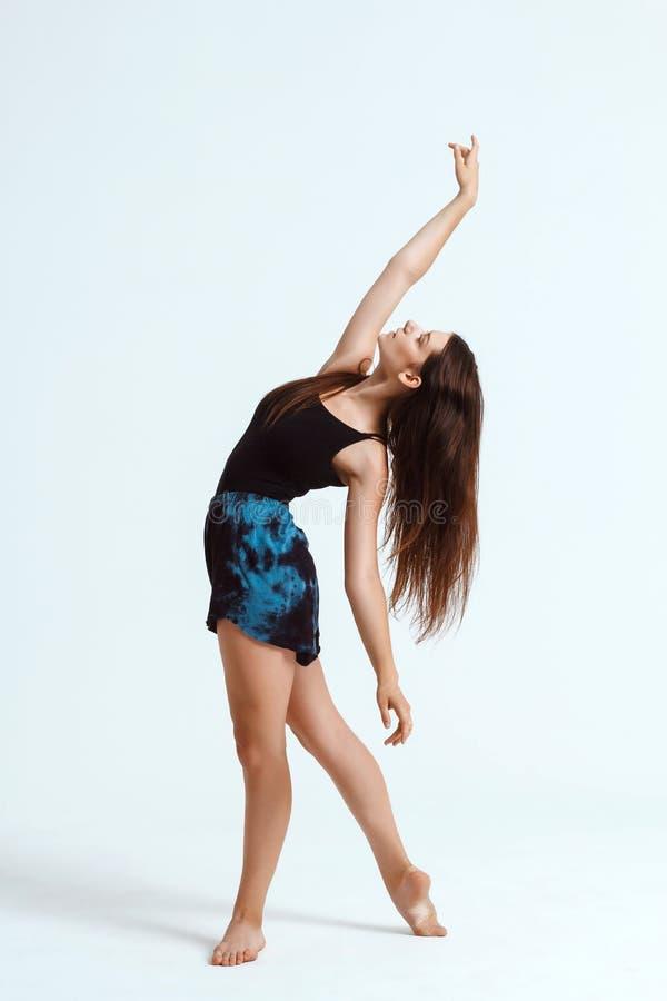 Dançarino contemporâneo bonito novo que levanta sobre o fundo branco Copie o espaço imagens de stock