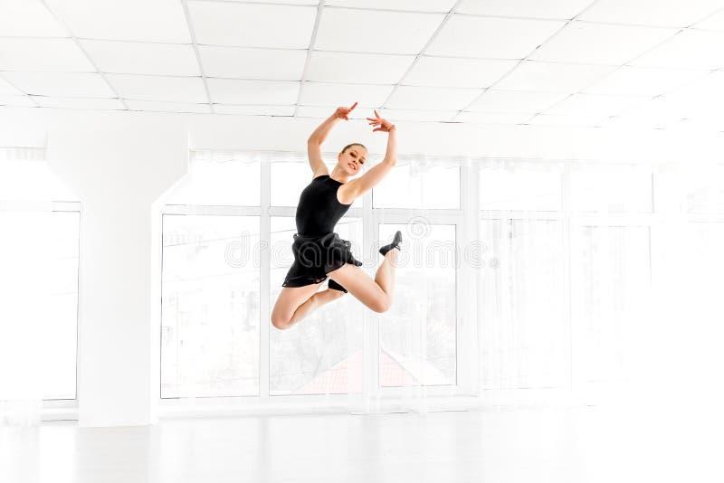 Dançarino da bailarina que executa um salto no estúdio branco foto de stock royalty free