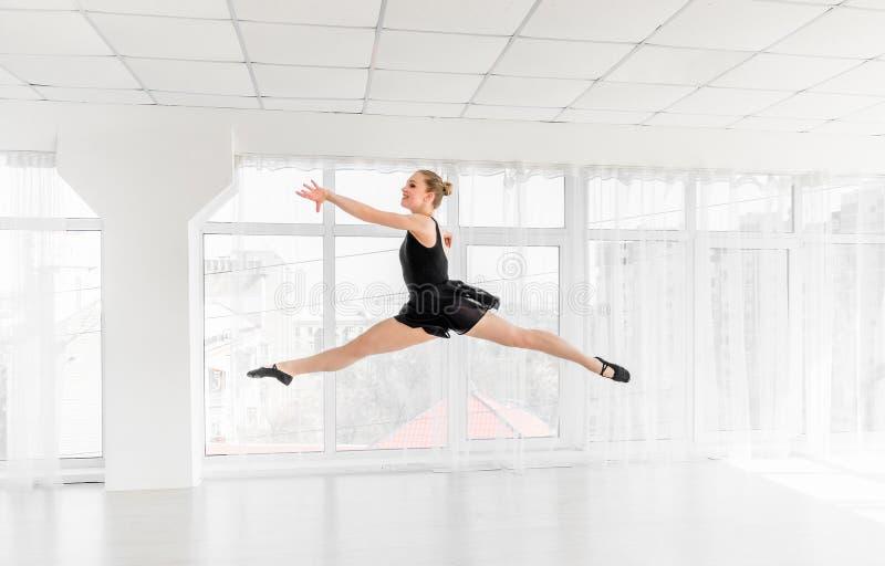 Dançarino da bailarina que executa um salto no estúdio branco fotografia de stock