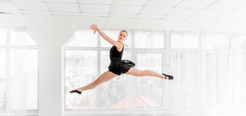 Dançarino da bailarina que executa um salto no estúdio branco imagens de stock royalty free