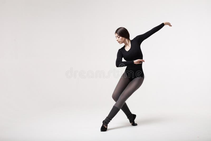 Dançarino da jovem mulher no levantamento preto do roupa de banho foto de stock