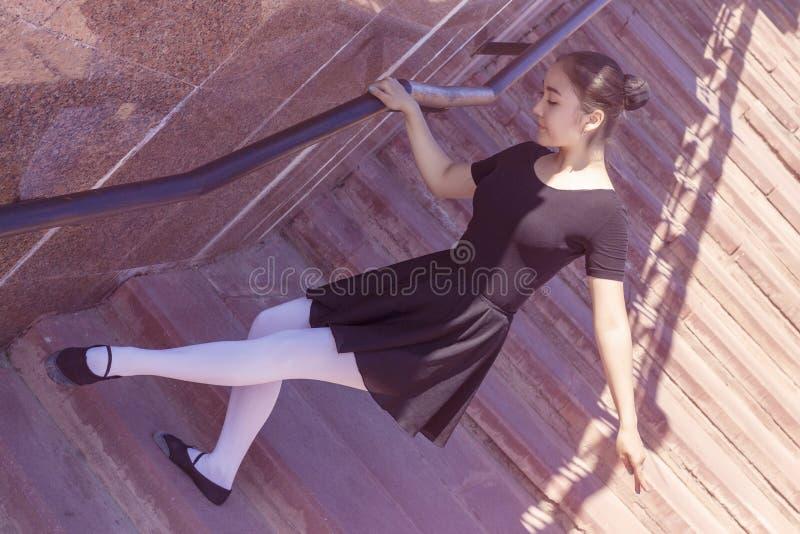 Dançarino da menina que faz movimentos diferentes da dança no maiô para sapatas da dança e de bailado fotografia de stock