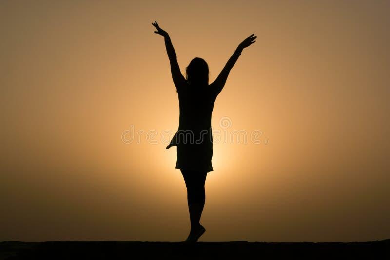 Dançarino de bailado With Arms Up da silhueta que enfrenta o por do sol imagens de stock