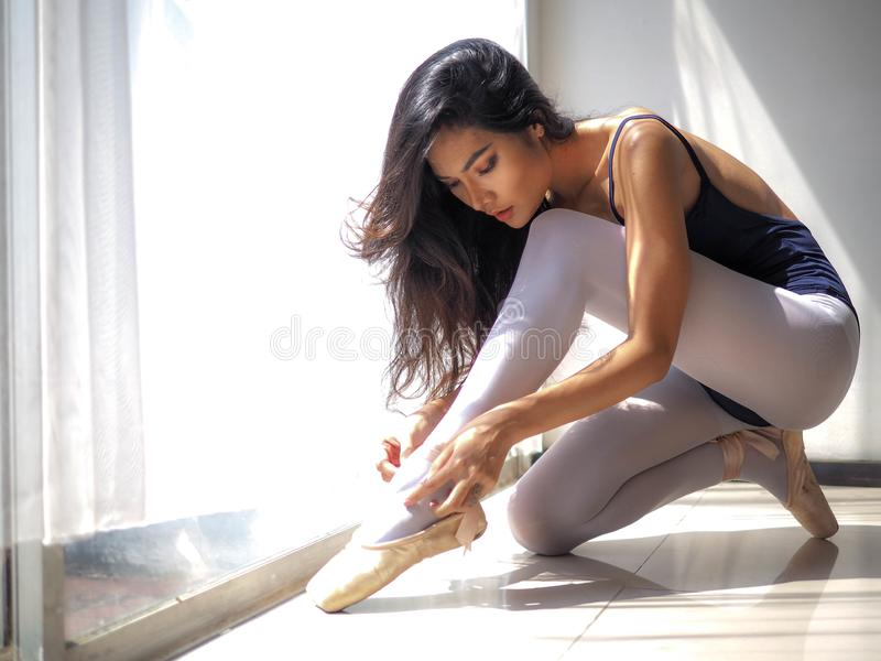 Dançarino de bailado bonito da mulher que senta-se no assoalho, pose bonita, foco principal nos pés fotografia de stock royalty free
