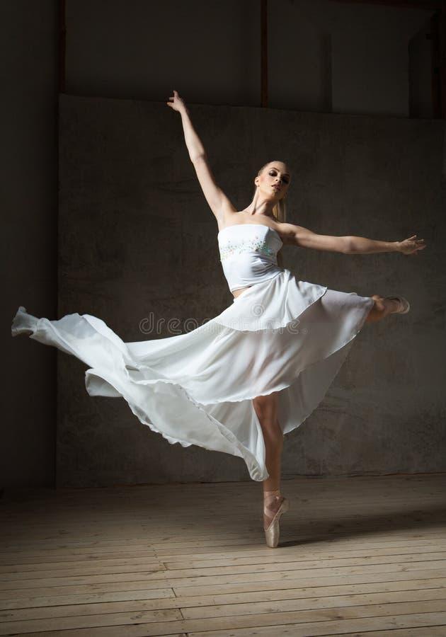 Dançarino de bailado bonito no traje branco com dança de ondulação da saia fotografia de stock royalty free