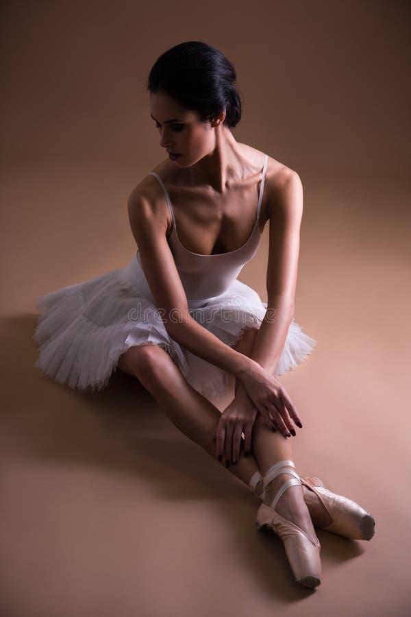 Dançarino de bailado bonito novo da mulher no assento do tutu imagem de stock royalty free