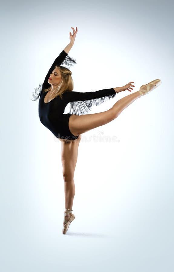 Dançarino de bailado bonito que faz um arabesque fotos de stock