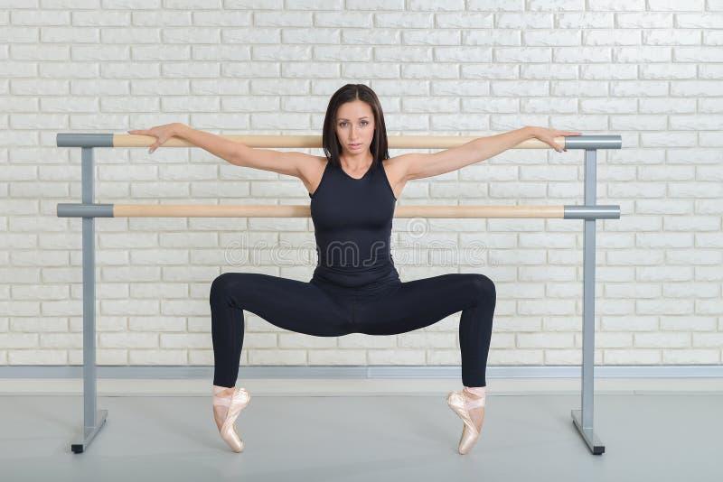 Dançarino de bailado bonito que pratica perto da barra no estúdio do bailado, retrato completo do comprimento da bailarina fotografia de stock