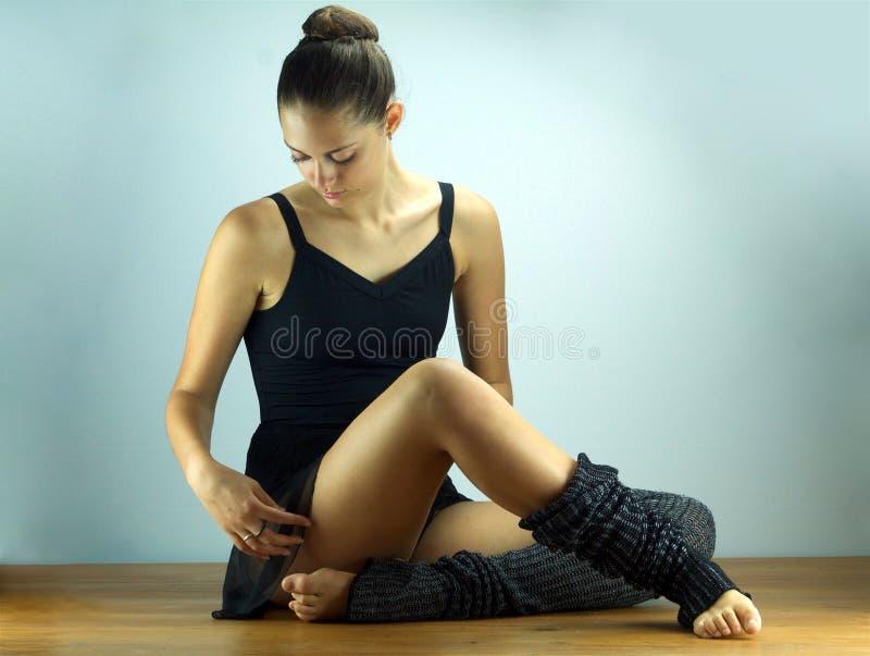 Dançarino de bailado bonito que senta-se no assoalho imagens de stock
