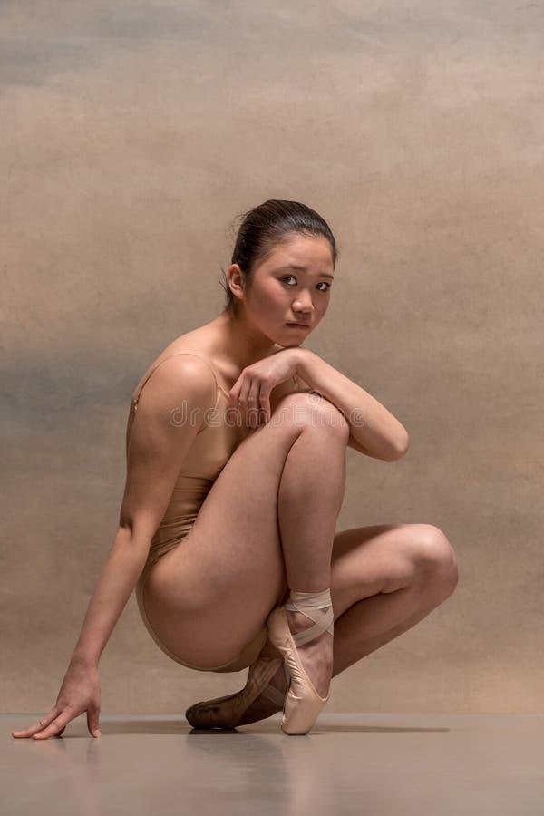 Dançarino de bailado cansado que senta-se na cadeira de madeira em um fundo cinzento foto de stock royalty free