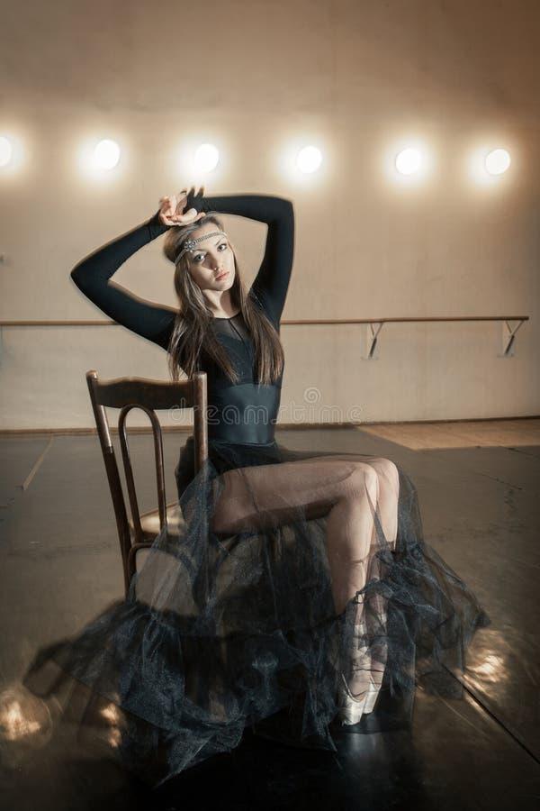 Dançarino de bailado contemporâneo em uma cadeira de madeira em uma repetição imagens de stock