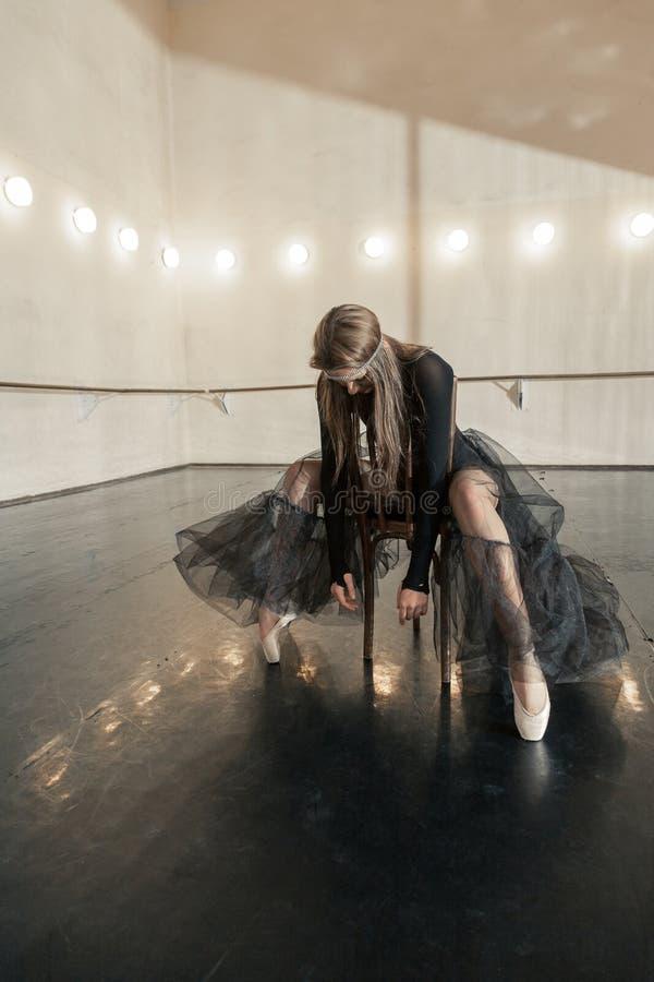 Dançarino de bailado contemporâneo em uma cadeira de madeira em uma repetição fotografia de stock