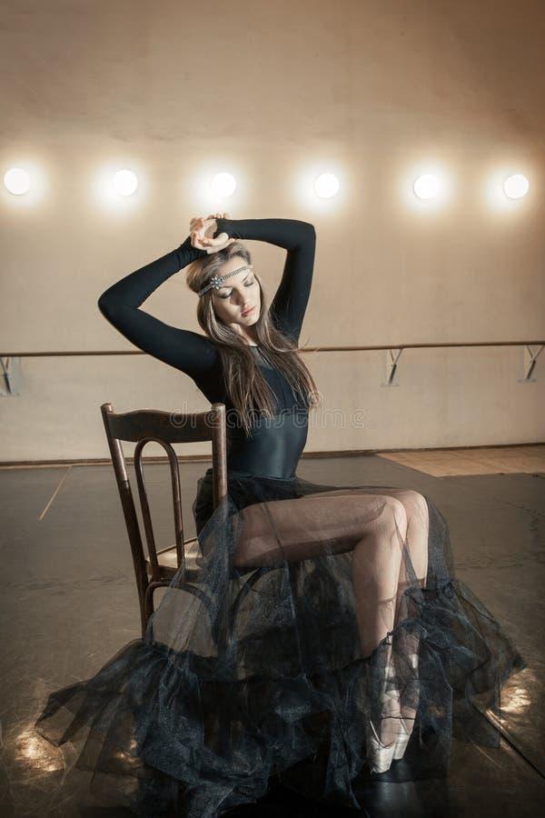Dançarino de bailado contemporâneo em uma cadeira de madeira em uma repetição imagem de stock royalty free
