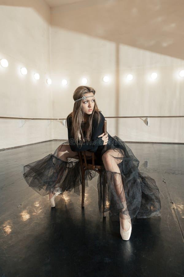 Dançarino de bailado contemporâneo em uma cadeira de madeira em uma repetição imagem de stock