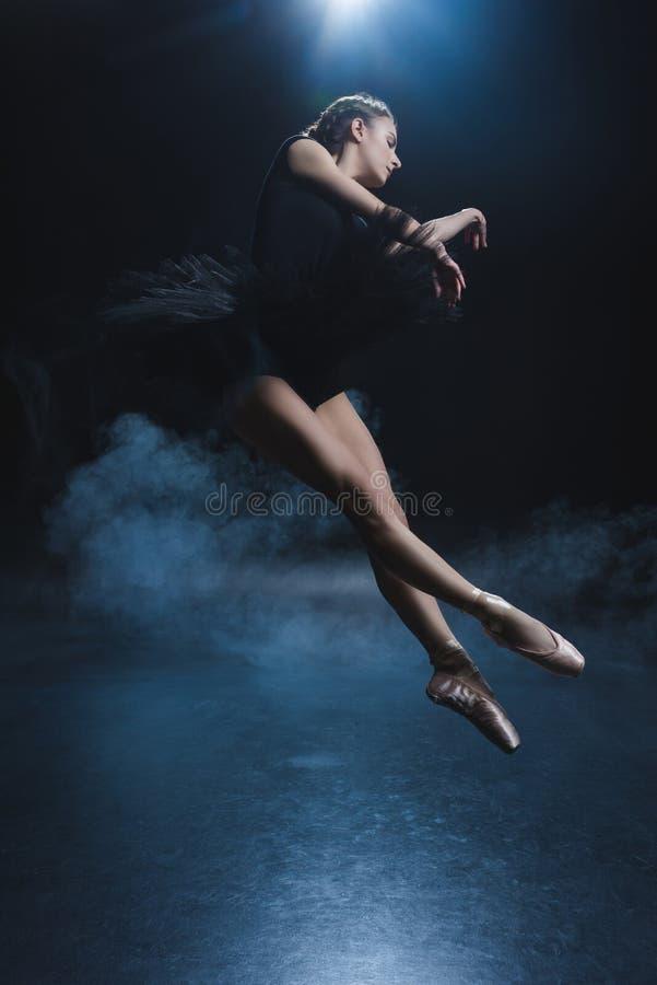 dançarino de bailado elegante atrativo em sapatas do pointe e no tutu preto no estúdio foto de stock