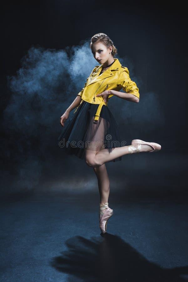 dançarino de bailado elegante em sapatas do pointe e no couro preto do tutu e o amarelo fotos de stock royalty free