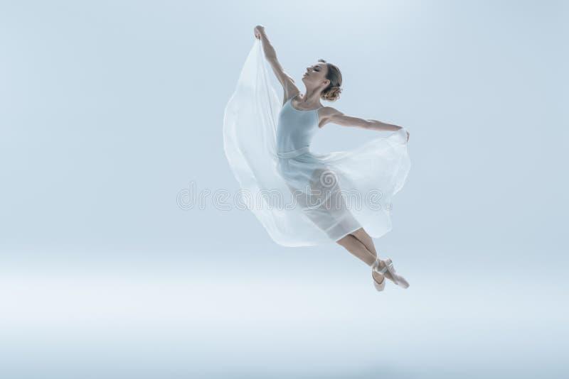 dançarino de bailado elegante no vestido branco que salta no estúdio imagens de stock royalty free