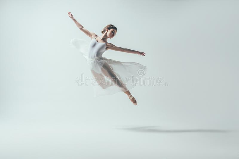 dançarino de bailado elegante no vestido branco que salta no estúdio foto de stock