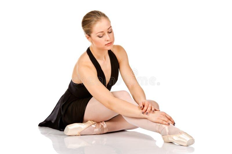 Dançarino de bailado elegante que senta-se no assoalho imagem de stock