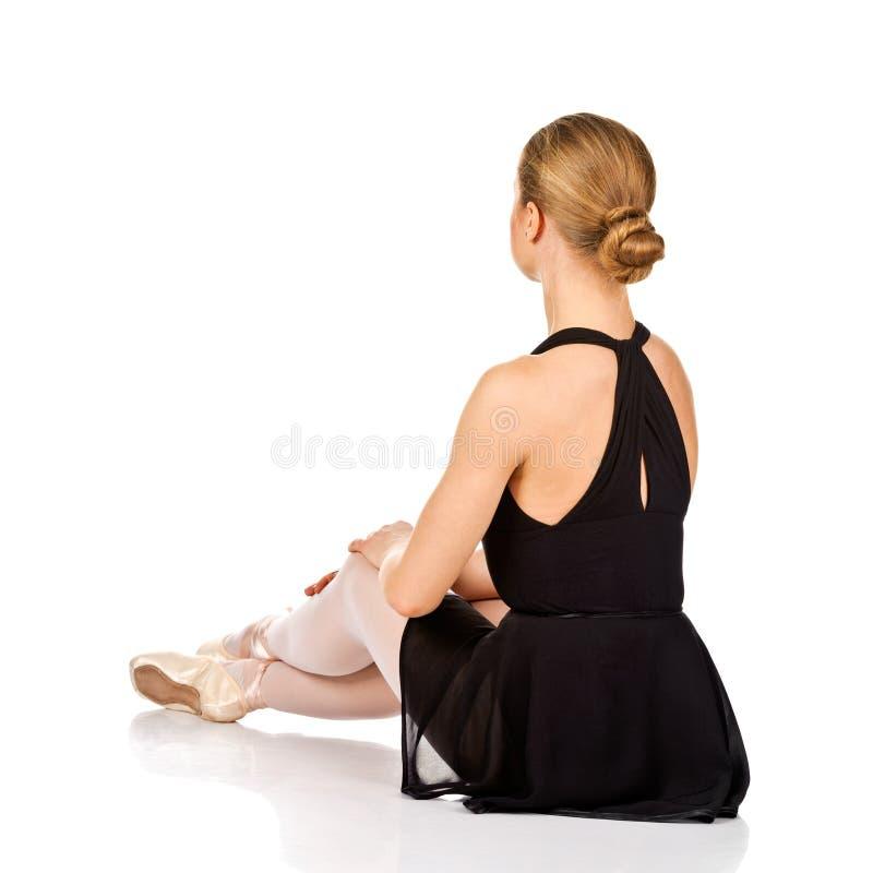 Dançarino de bailado elegante que senta-se no assoalho. Vista traseira fotografia de stock royalty free