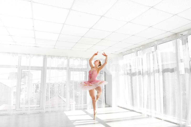 Dançarino de bailado fêmea elegante no tutu cor-de-rosa que pratica e que sorri fotografia de stock royalty free