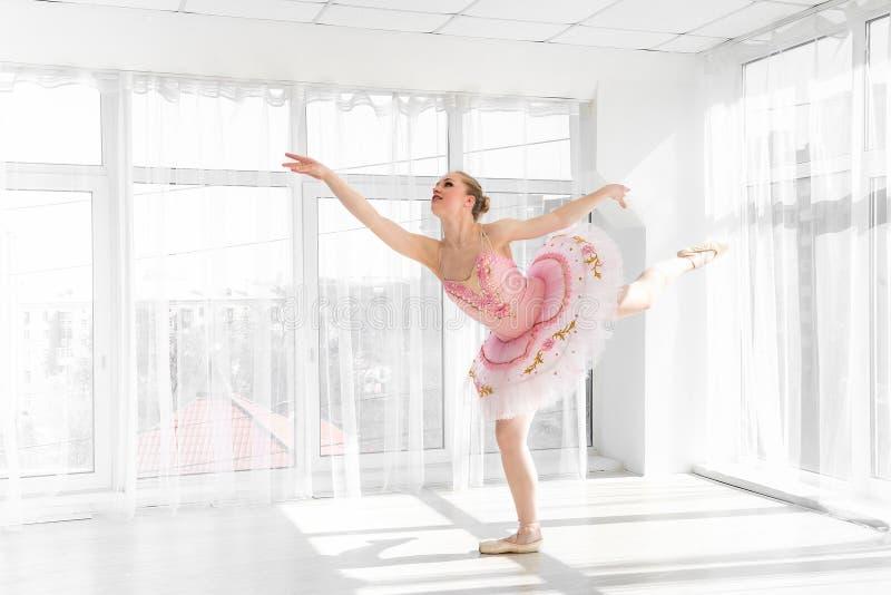 Dançarino de bailado fêmea elegante no tutu cor-de-rosa que pratica e que sorri imagens de stock royalty free