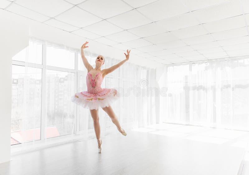 Dançarino de bailado fêmea elegante no tutu cor-de-rosa que pratica e que sorri foto de stock
