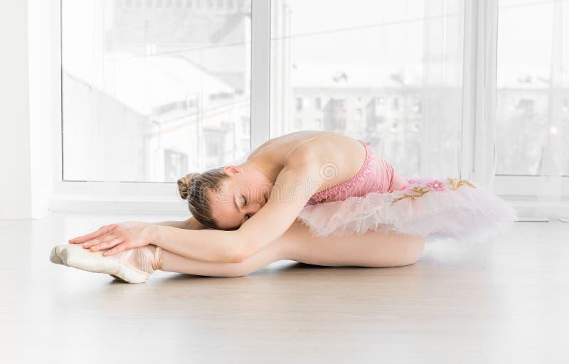 Dançarino de bailado fêmea elegante no tutu cor-de-rosa que pratica e que sorri fotografia de stock