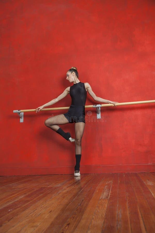 Dançarino de bailado fêmea Practicing At Bar no estúdio fotografia de stock