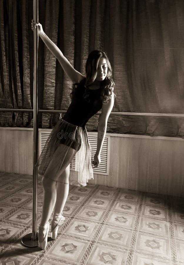 Dançarino de bailado flexível que estica no estilo retro A bailarina dança perto do polo imagem de stock
