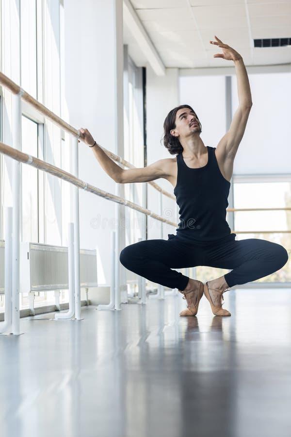 Dançarino de bailado masculino novo Posing Near Barre, homem que pratica dentro fotografia de stock royalty free