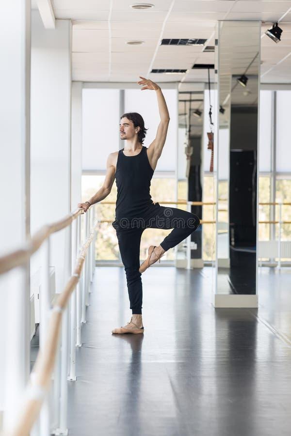 Dançarino de bailado masculino novo Posing Near Barre, praticar do homem foto de stock royalty free