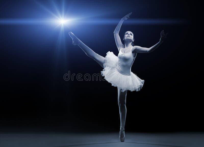 Dançarino de bailado no tutu branco que levanta em um pé fotografia de stock