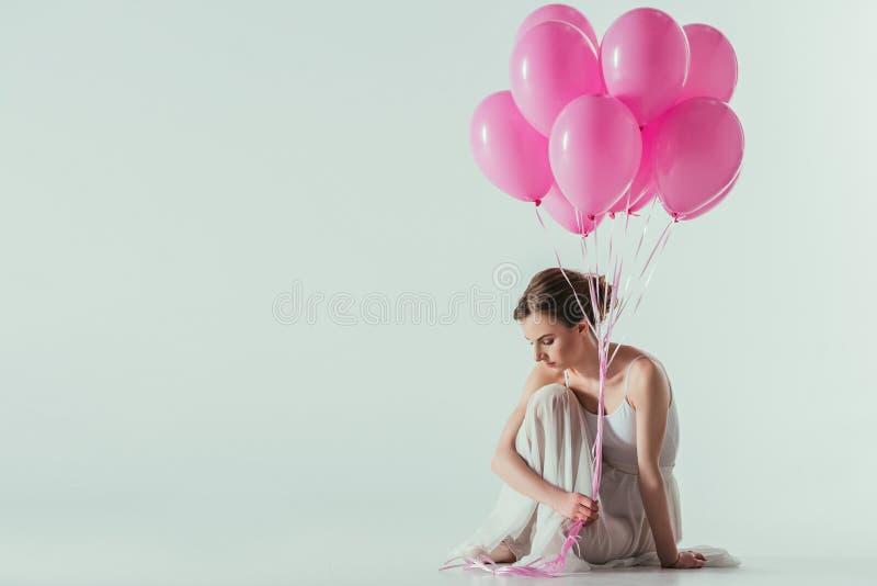 dançarino de bailado no vestido branco que senta-se com balões cor-de-rosa fotografia de stock