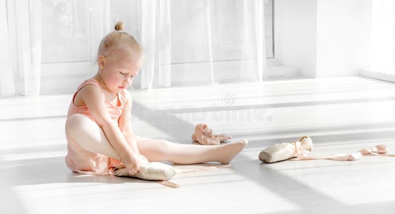 Dançarino de bailado novo no tutu que senta-se no assoalho e que amarra sapatas do pointe fotos de stock