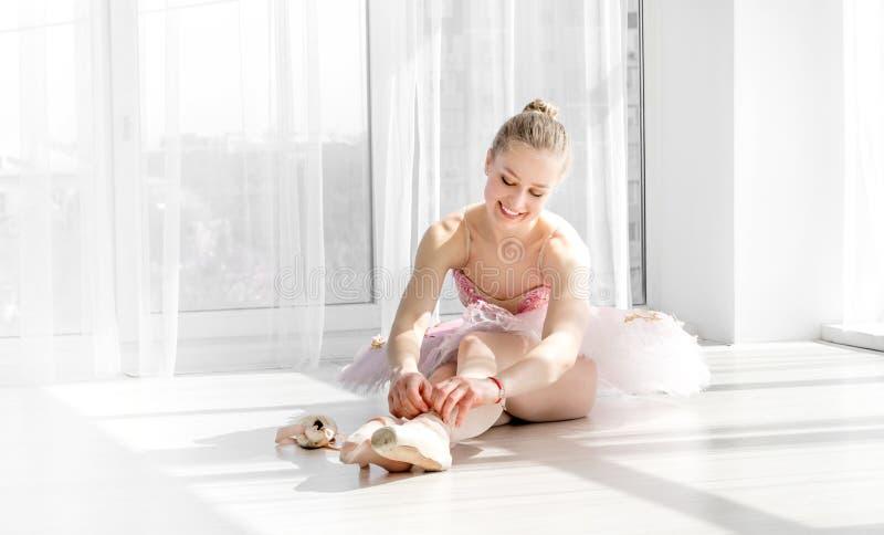 Dançarino de bailado novo no tutu que senta-se no assoalho e que amarra sapatas do pointe imagens de stock royalty free