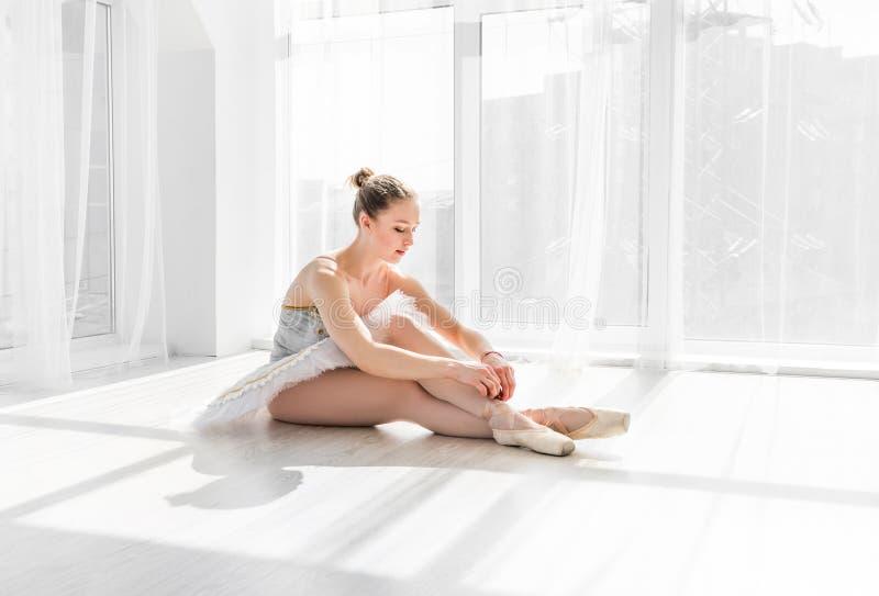 Dançarino de bailado novo no tutu que senta-se no assoalho e que amarra sapatas do pointe fotografia de stock