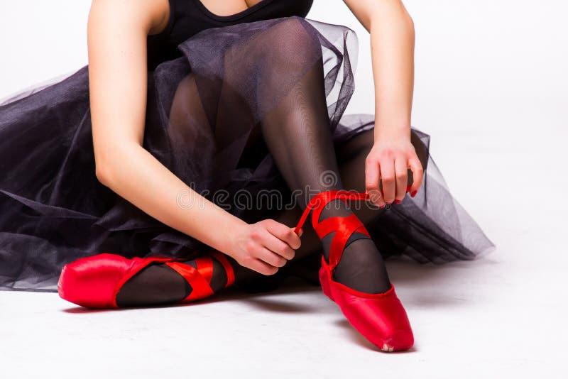 Dançarino de bailado que amarra deslizadores vermelhos em torno de seu tornozelo fotos de stock royalty free