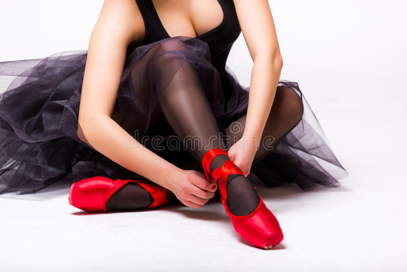 Dançarino de bailado que amarra deslizadores vermelhos em torno de seu tornozelo fotografia de stock