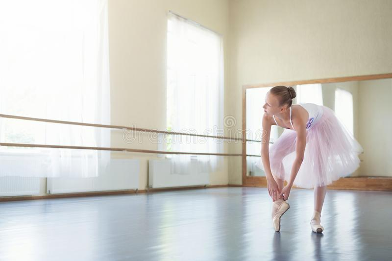 Dançarino de bailado que amarra sapatas do pointe no estúdio claro imagem de stock
