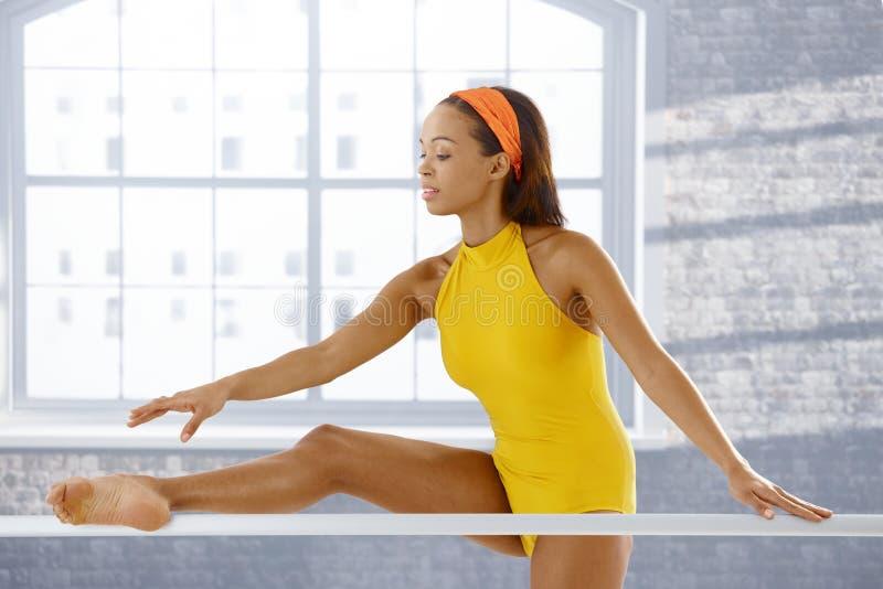 Dançarino de bailado que estica na barra imagem de stock
