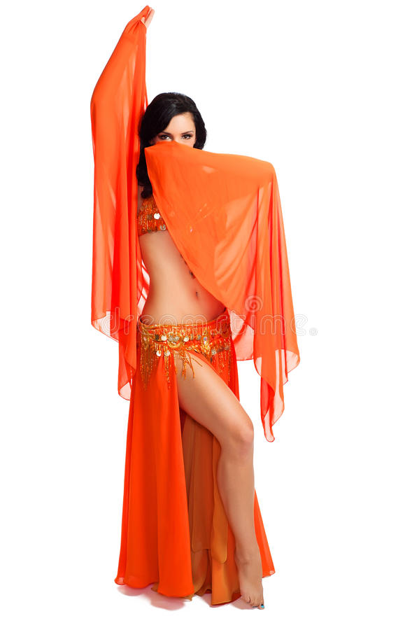Dançarino de barriga que desgasta o traje e o véu alaranjados fotografia de stock royalty free