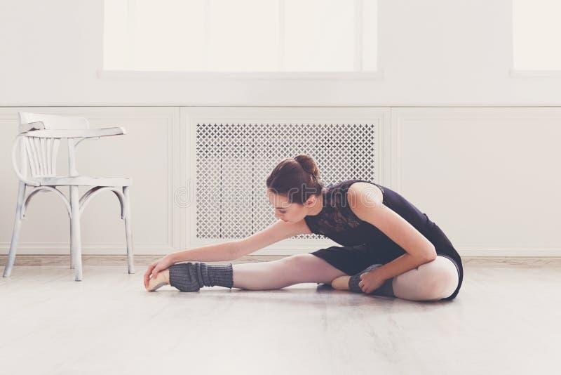 Dançarino do balé clássico que estica na classe de treinamento branca foto de stock