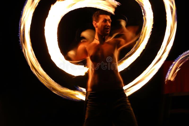 Dançarino do fogo na noite em um acampamento fotografia de stock