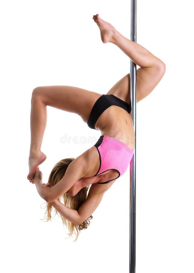 Dançarino fêmea flexível que equilibra no polo fotos de stock royalty free