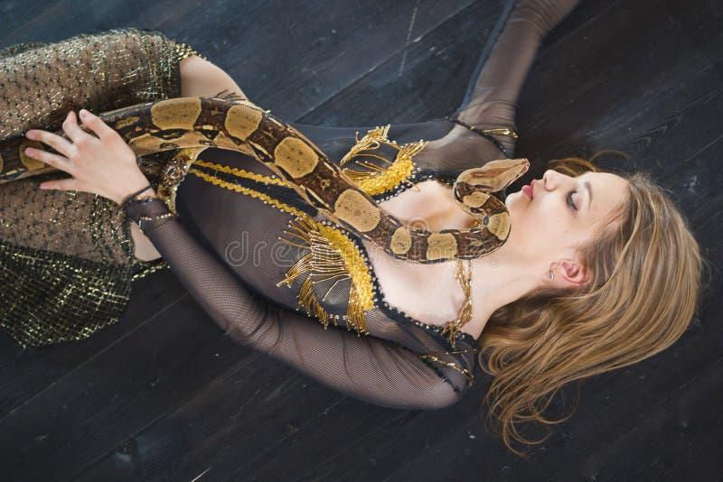 Dançarino fêmea novo que encontra-se no assoalho com uma serpente em seu corpo fotografia de stock royalty free