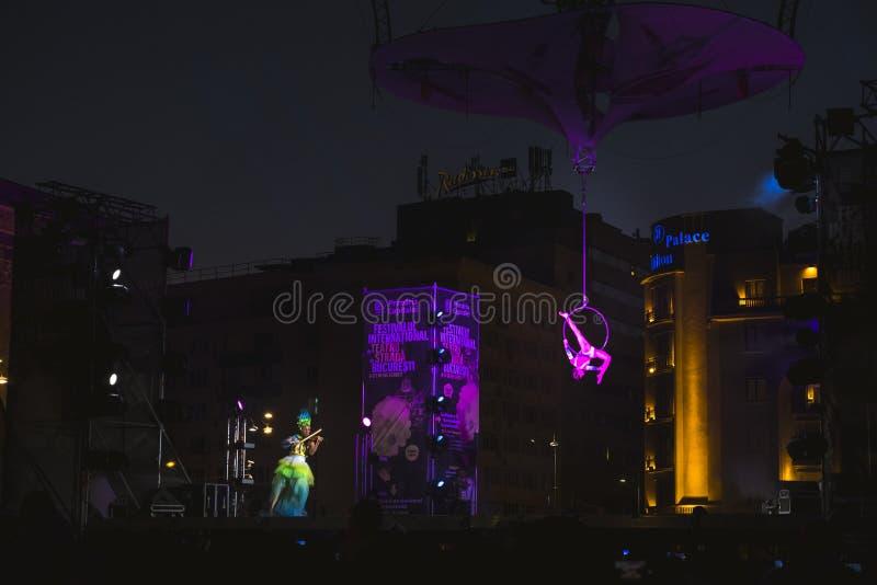 Dançarino gracioso que executam a acrobacia aérea e jogador bonito do violino no festival do teatro da rua em Bucareste fotos de stock